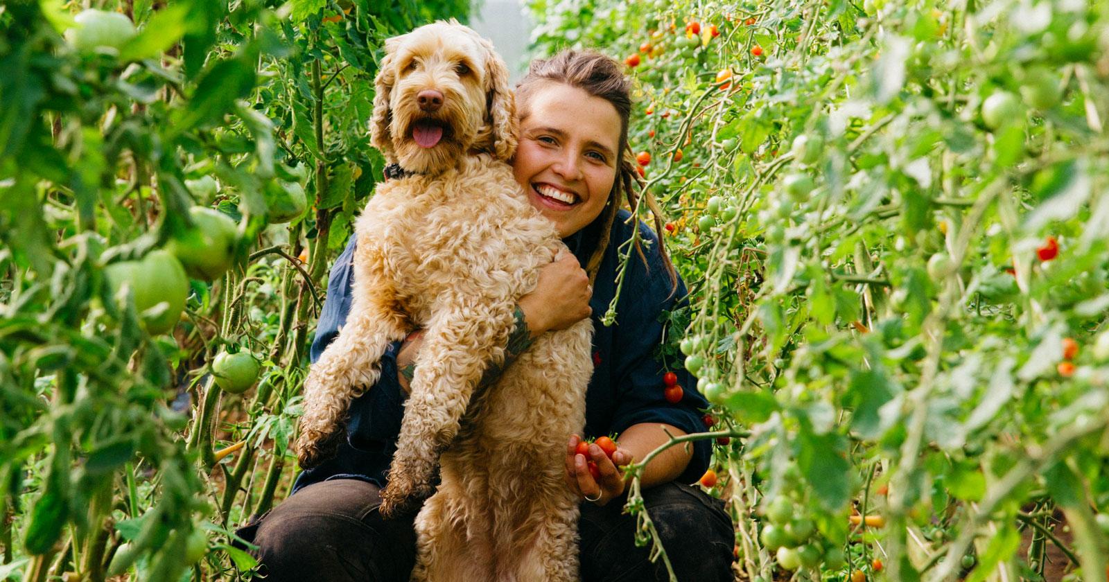 Angelika med sin hund Valle i växthuset på Angelikas gård på Österlen